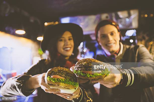 Friends in fast food restaurant, holding burgers