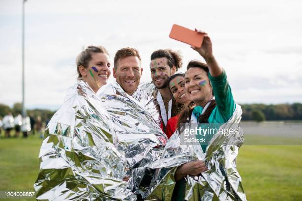 friends in foil blankets taking selfie at charity event - charity benefit stock pictures, royalty-free photos & images