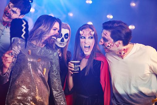 Friends in Halloween costumes dancing among confetti - gettyimageskorea