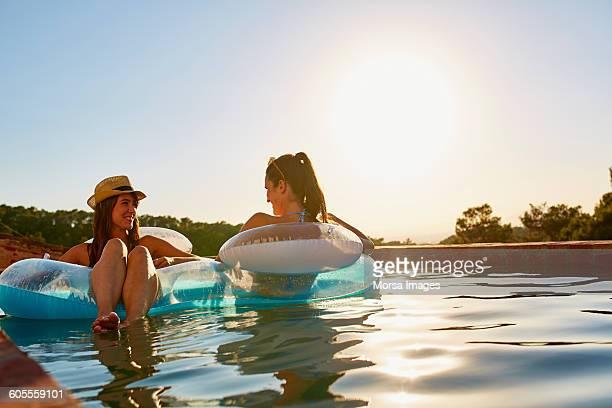 friends in inflatable ring floating on pool - nur erwachsene stock-fotos und bilder