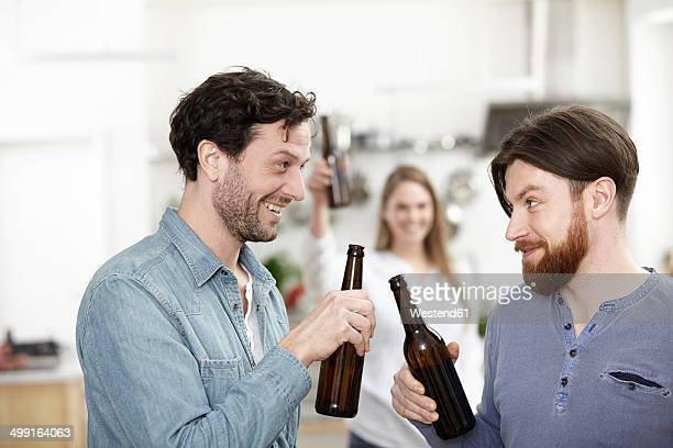Friends in kitchen drinking beer