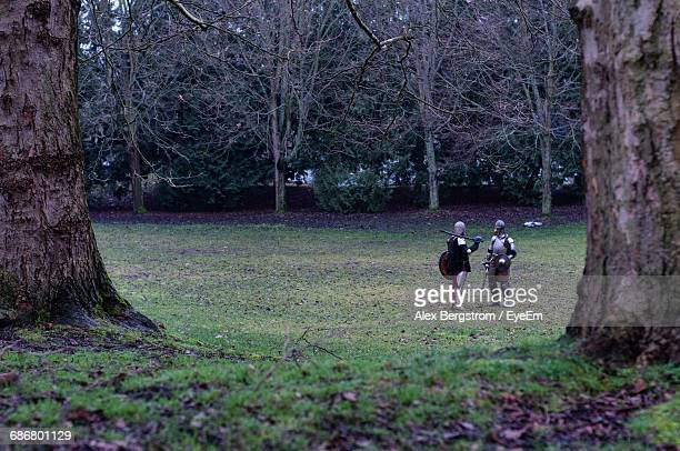 Friends In Knight Costume Standing On Grassy Field Against Trees