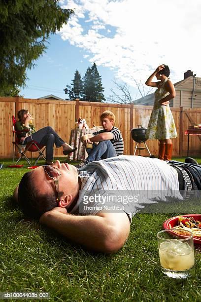 Friends in lawn, man lying on grass