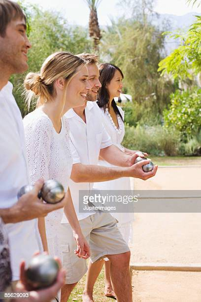 Friends in line holding bocce balls