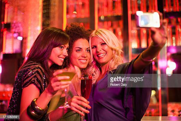 Friends in nightclub taking self-portrait with digital camera
