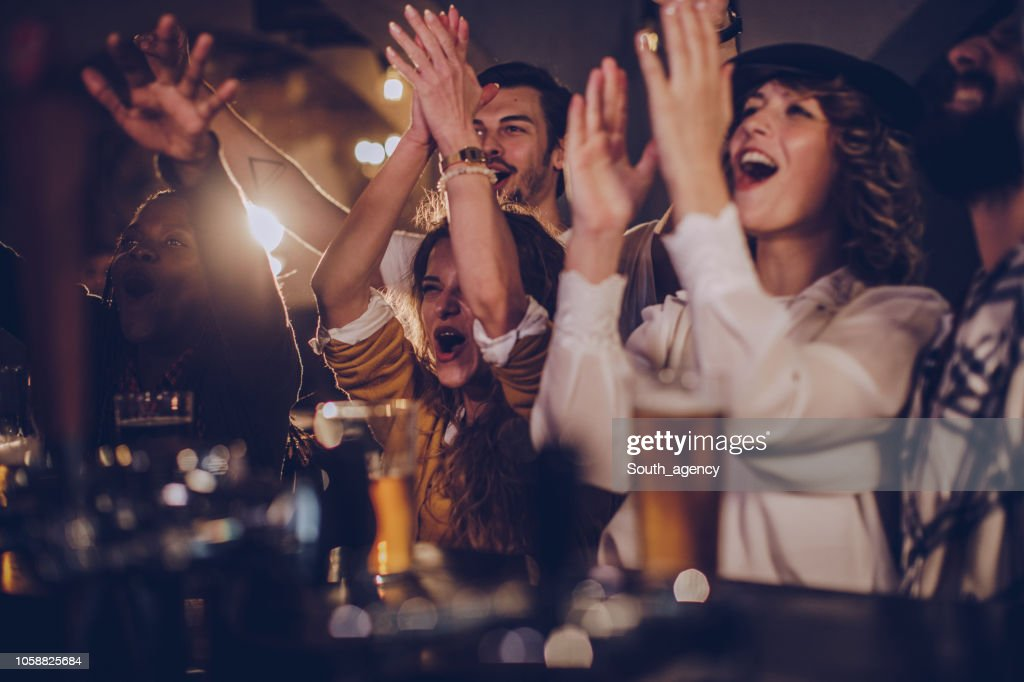 Friends in pub watching match : Stock Photo