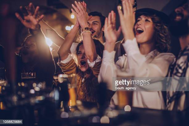 friends in pub watching match - cheering stock pictures, royalty-free photos & images