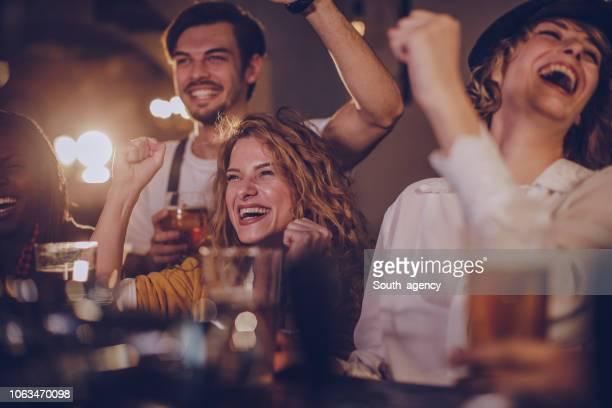 amigos no bar assistindo jogo - taking a shot sport - fotografias e filmes do acervo