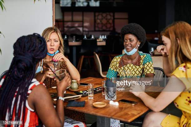 friends in restaurant with face masks - new normal friendship concept - chin stock pictures, royalty-free photos & images