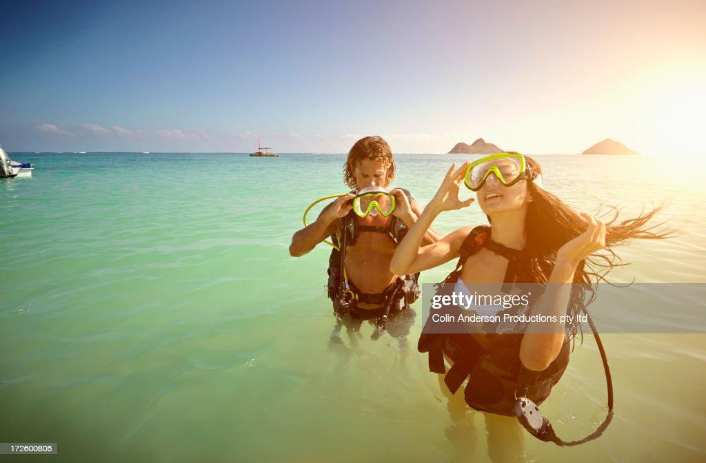 Friends in scuba gear standing in ocean
