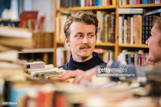 friends in second hand bookstore - literature stock photos and pictures