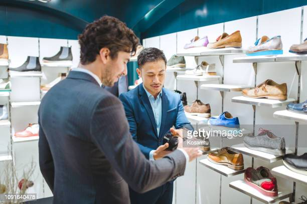 friends in shoe store buying new shoes - multi colored suit stock photos and pictures