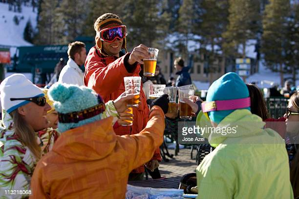 Friends in ski gear socialize and enjoy a beer on the deck on a sunny day on the mountain.