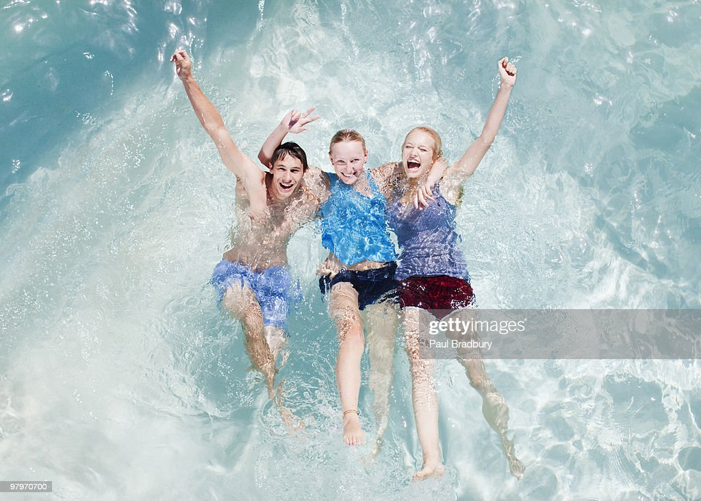 Friends in swimming pool with arms raised : Stock Photo