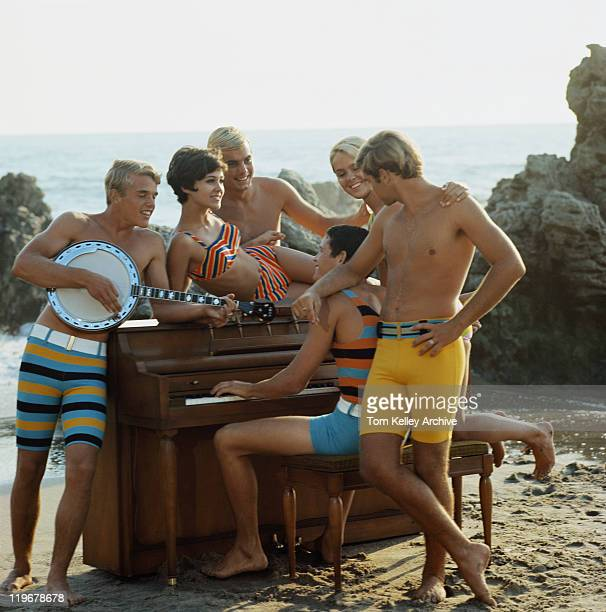 Friends in swimwear playing guitar and piano on beach