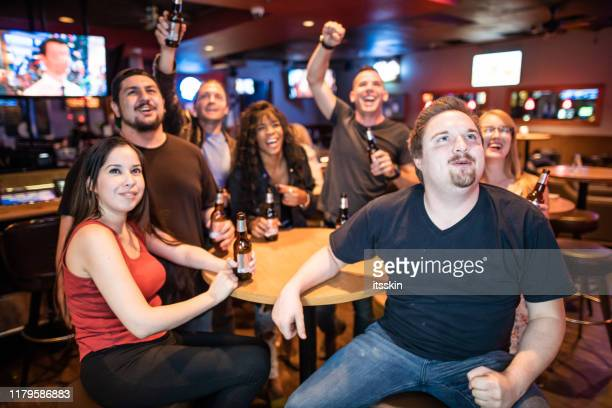amis dans le bar observant des sports et buvant la bière - american football sport photos et images de collection