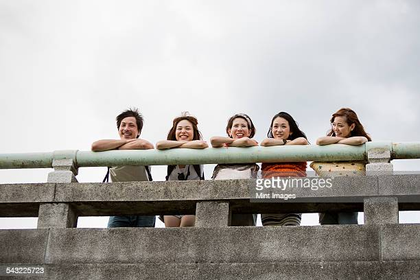 Friends in the park leaning on a parapet. View from below.