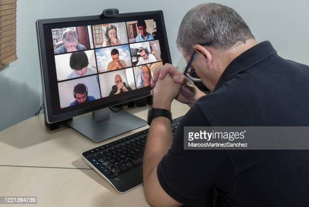 friends in their homes on a conference call and praying together for the good of all - lowering the head - praying stock pictures, royalty-free photos & images