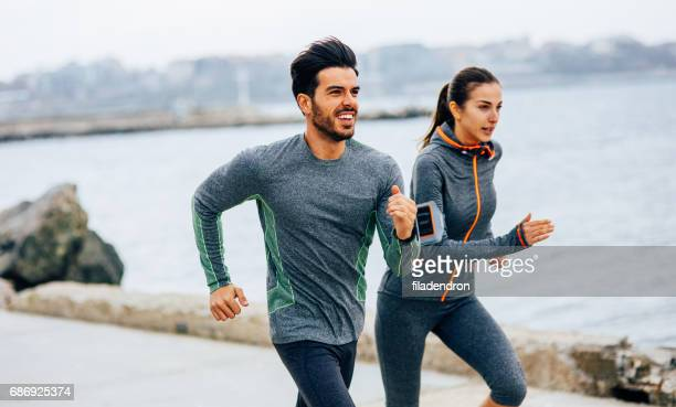 friends jogging by the sea - running stock pictures, royalty-free photos & images