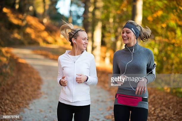 Friends jogging in autumn outdoor park