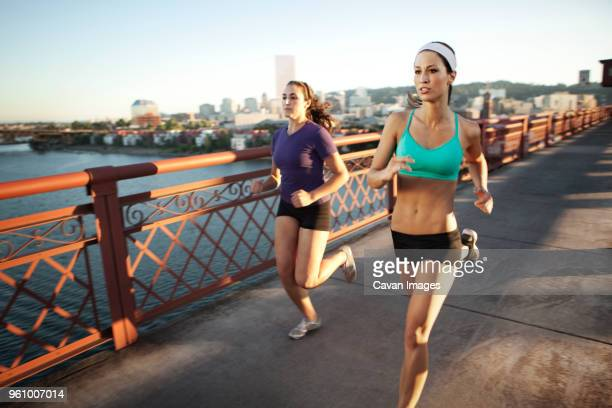 friends jogging on bridge - bra top stock pictures, royalty-free photos & images