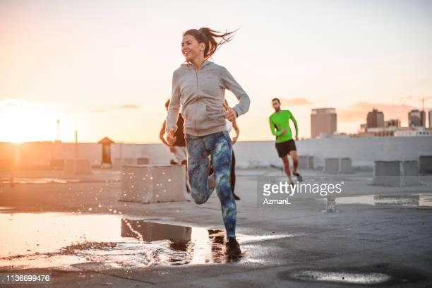vrienden joggen samen op het terras tegen de hemel - joggen stockfoto's en -beelden