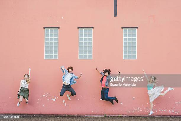 friends jumping against pink wall background - pink pants stock pictures, royalty-free photos & images