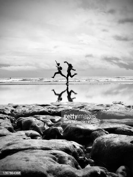friends jumping at beach against cloudy sky - black and white stock pictures, royalty-free photos & images