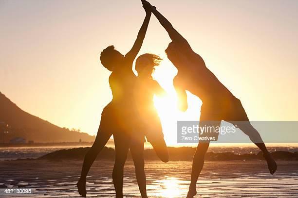 Friends jumping by seaside