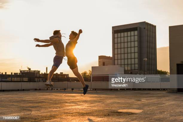 Friends jumping for joy at sunset