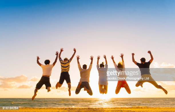 Friends jumping for joy on beach at sunset
