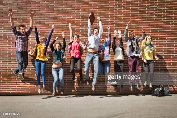 friends jumping for joy on city street - groupe moyen de personnes photos et images de collection
