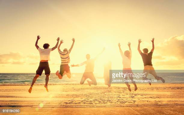 Friends jumping for joy on sunny beach