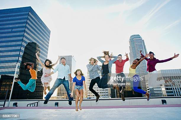 Friends jumping for joy on urban rooftop