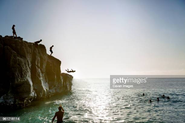 friends jumping from cliff to sea against sky - klippe stock-fotos und bilder
