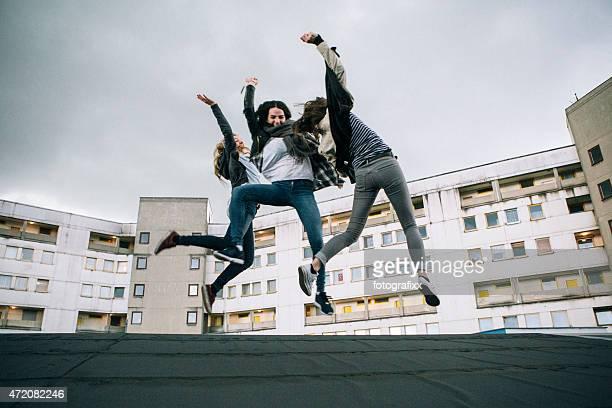 Friends jumping high in front of urban background