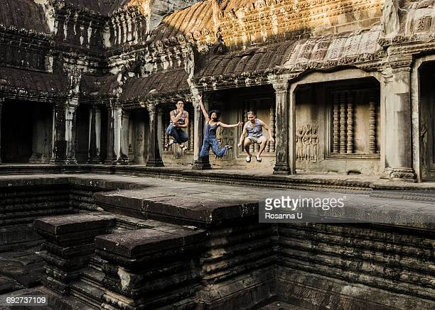 Friends jumping in mid air, Angkor Wat temple, Siem Reap, Cambodia