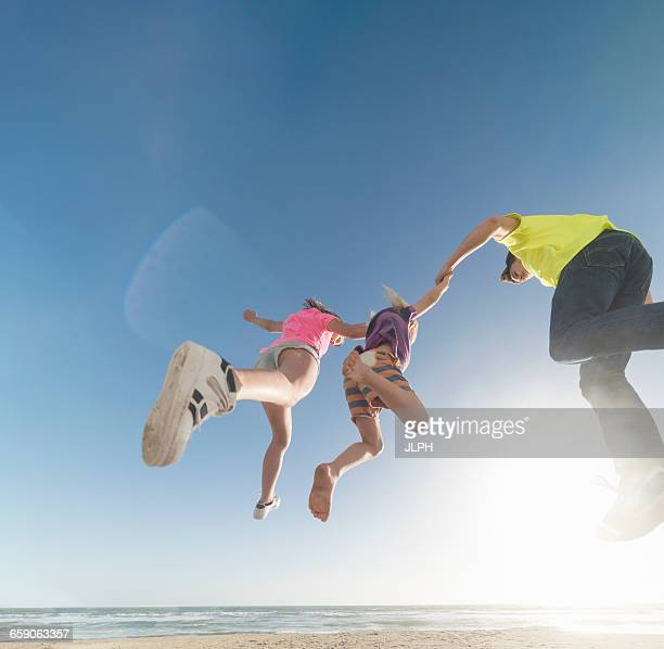 Friends jumping in mid air by sea
