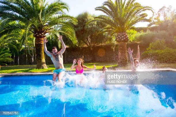 Friends jumping in swimming pool, splashing