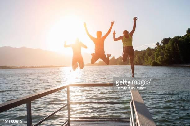 friends jumping into a lake together - bootssteg stock-fotos und bilder