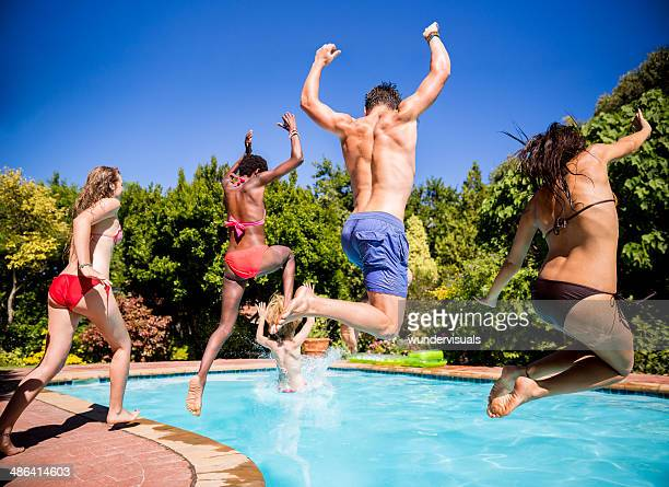 Friends jumping into a pool