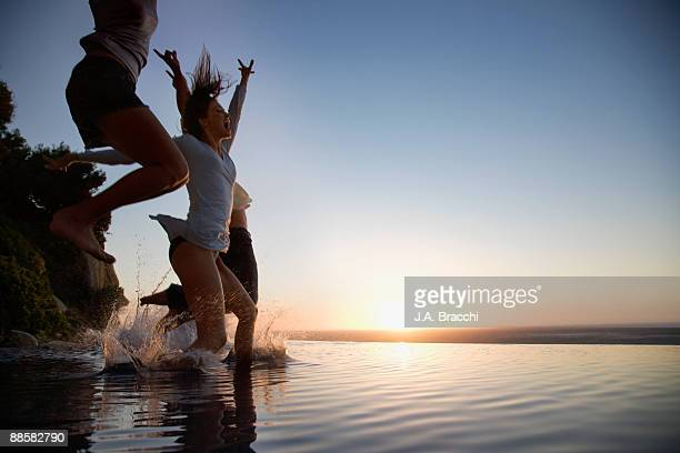 Friends jumping into infinity pool at sunset