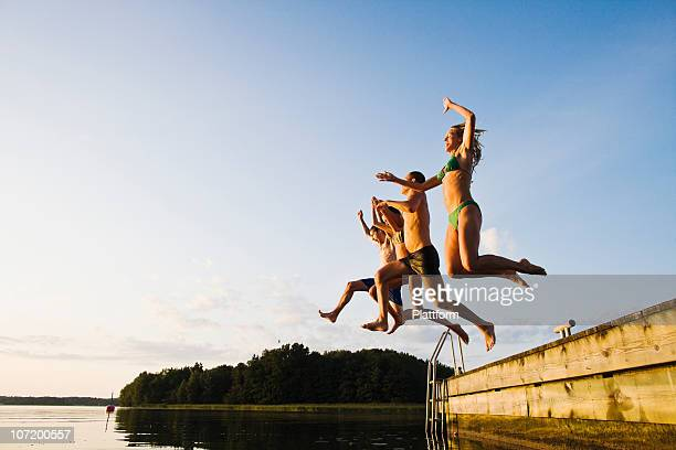 friends jumping into lake - lake stock pictures, royalty-free photos & images
