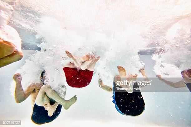 Friends jumping into pool together underwater view