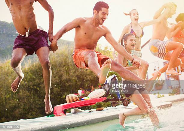 friends jumping into swimming pool at pool party - pool party stock pictures, royalty-free photos & images