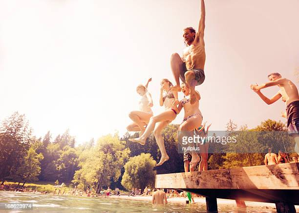 friends jumping into the water