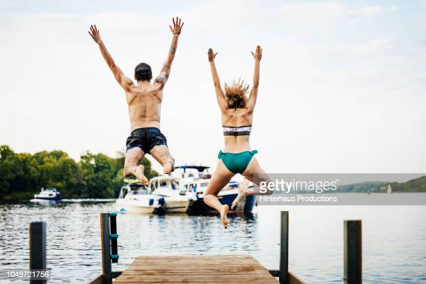 Friends Jumping Into Water Off Pier Together