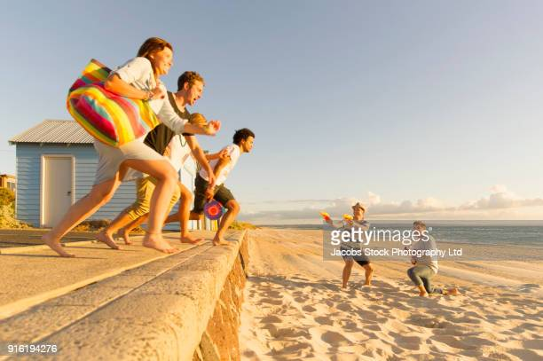 Friends jumping of wall onto beach