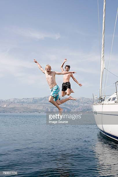 Friends jumping off a yacht