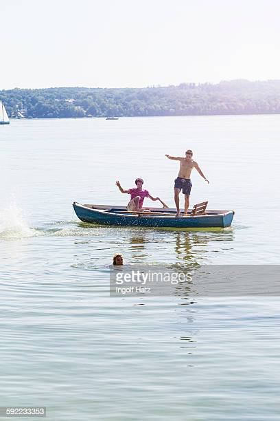 Friends jumping off boat and swimming in lake, Schondorf, Ammersee, Bavaria, Germany